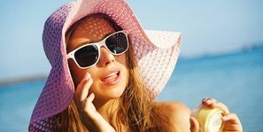 best natural sunscreen for the face - a woman in hat with sunscreen on